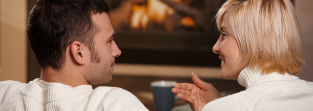 Couple shown chatting by the fire